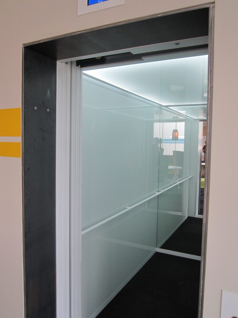Auskleidung einer Aufzugskabine mit weiß gepulverten ESG-Glas